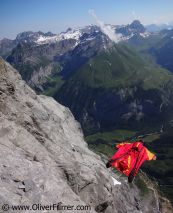 BASE jumper is flying with his wingsuit along the cliff